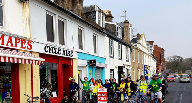 Group of people on bikes outside cycle hire shop on Milport