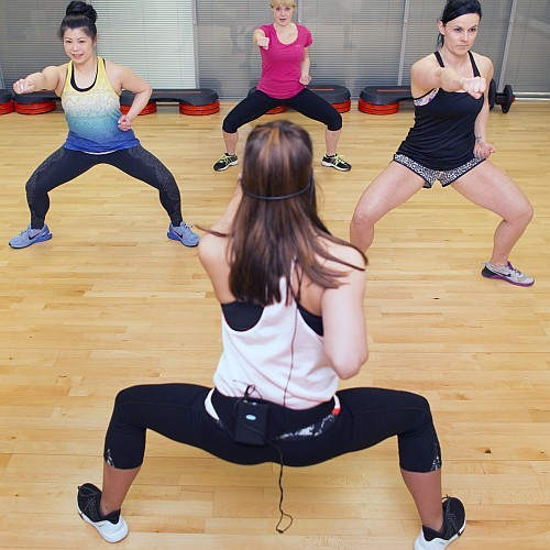 3 woman facing instructor working out during body attack class